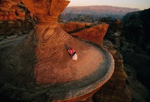 A Bedouin man sitting on top of one of the ancient buildings of Petra ( Jordan), photo by Annie Griffiths